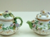 A selection of flower encrusted Rockingham teapots